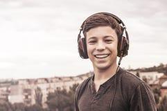 Adolescente en el tejado de la casa en los auriculares Fotografía de archivo libre de regalías