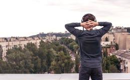 Adolescente en el tejado de la casa en los auriculares Imagenes de archivo