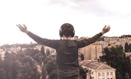 Adolescente en el tejado de la casa en los auriculares foto de archivo libre de regalías