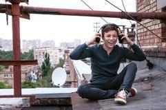 Adolescente en el tejado de la casa en los auriculares Fotos de archivo