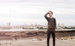 Adolescente en el tejado de un edificio alto Imagen de archivo
