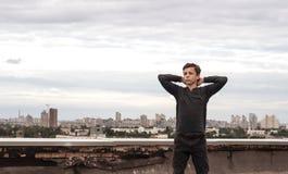 Adolescente en el tejado de un edificio alto Foto de archivo