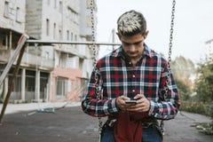 Adolescente en el teléfono móvil en parque Imagen de archivo libre de regalías