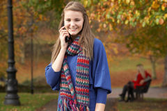 Adolescente en el teléfono móvil en parque del otoño Fotografía de archivo