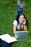 Adolescente en el teléfono que coloca en la hierba Imágenes de archivo libres de regalías