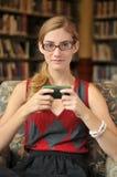 Adolescente en el teléfono texting en biblioteca Foto de archivo