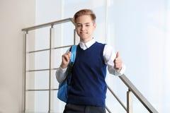 Adolescente en el uniforme escolar que muestra el pulgar encima de la situación del gesto Fotos de archivo libres de regalías
