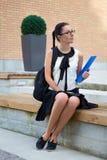 Adolescente en el uniforme escolar que se sienta en banco Fotos de archivo