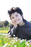 Adolescente en el verde en el parque Foto de archivo