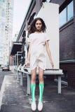 Adolescente en el vestido blanco que salta en la calle Imágenes de archivo libres de regalías