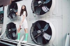 Adolescente en el vestido blanco que se coloca en la construcción de la fan Fotos de archivo libres de regalías