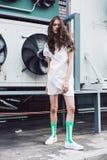 Adolescente en el vestido blanco y calcetines verdes en la calle Fotos de archivo libres de regalías
