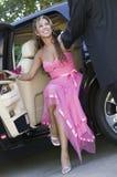 Adolescente en el vestido que es ayudado fuera del limo Imágenes de archivo libres de regalías