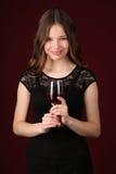 Adolescente en el vestido que sostiene el vidrio de vino Cierre para arriba Fondo rojo oscuro Imagenes de archivo