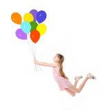 Adolescente en el vuelo rosado del vestido en los globos Imagenes de archivo