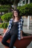 Adolescente en equipo casual con smartphone y auriculares al aire libre en parque Foto de archivo libre de regalías