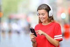 Adolescente en escuchar rojo la música en línea en la calle Fotos de archivo
