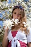 Adolescente en flores de la magnolia Fotografía de archivo libre de regalías