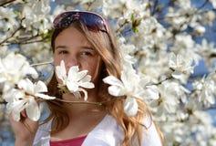 Adolescente en flores de la magnolia Fotografía de archivo