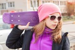 Adolescente en gafas de sol con el monopatín Fotos de archivo libres de regalías