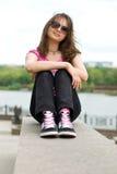 Adolescente en gafas de sol y zapatillas de deporte Foto de archivo