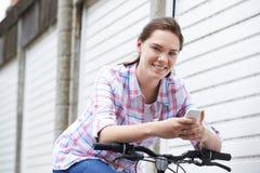 Adolescente en la bici que manda un SMS en el teléfono móvil Fotografía de archivo