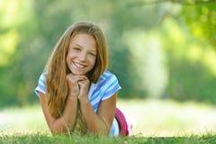 Adolescente en la blusa azul que miente en hierba Foto de archivo libre de regalías