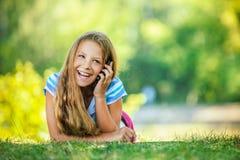 Adolescente en la blusa azul que miente en hierba Imagen de archivo