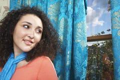 Adolescente en la bufanda que mira hacia fuera la ventana Foto de archivo libre de regalías