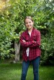 Adolescente en la camisa a cuadros roja que presenta en el jardín de la manzana Foto de archivo libre de regalías