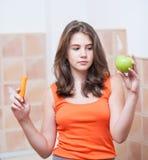 Adolescente en la camiseta anaranjada que come frutas en sus manos Fotos de archivo libres de regalías