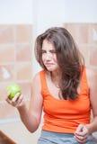 Adolescente en la camiseta anaranjada que intenta comer una manzana verde Imagenes de archivo