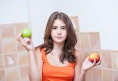 Adolescente en la camiseta anaranjada que mira la cámara que come una manzana verde y un melocotón en sus manos Fotografía de archivo libre de regalías