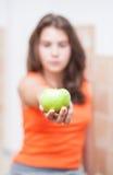 Adolescente en la camiseta anaranjada que muestra una manzana verde Foto de archivo
