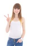 Adolescente en la camiseta blanca que muestra la muestra de la victoria aislada en w Fotos de archivo libres de regalías