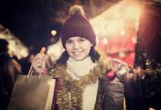 Adolescente en la capa que presenta en el mercado de Navidad Imágenes de archivo libres de regalías