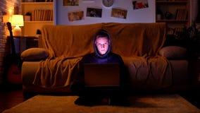 Adolescente en la capilla que juega al juego en el ordenador port?til o que rompe la p?gina web, ataque cibern?tico imagenes de archivo