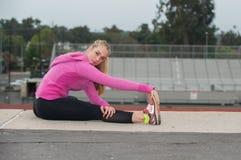 Adolescente en la chaqueta rosada que estira los tendones de la corva sobre campo Fotos de archivo