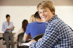 Adolescente en la clase que sonríe a la cámara Imágenes de archivo libres de regalías