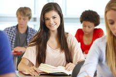 Adolescente en la clase que sonríe a la cámara Foto de archivo libre de regalías
