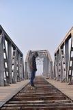 Adolescente en la depresión que se sienta en el puente en la puesta del sol Imágenes de archivo libres de regalías