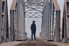 Adolescente en la depresión que se sienta en el puente en la puesta del sol Fotografía de archivo libre de regalías