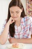 Adolescente en la dieta que mira el buñuelo Foto de archivo