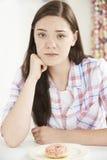 Adolescente en la dieta que mira el buñuelo Imagen de archivo