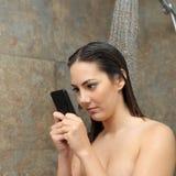 Adolescente en la ducha obsesionada con el teléfono elegante Fotos de archivo