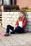 Adolescente en la falda roja que se sienta en la acera Fotos de archivo libres de regalías