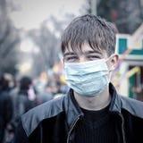 Adolescente en la máscara de la gripe Foto de archivo