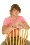 Adolescente en la mirada que se sienta de la camisa rosada Imágenes de archivo libres de regalías