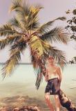 Adolescente en la palmera y océano en el fondo, con un efecto retro Fotos de archivo