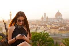 Adolescente en la puesta del sol en Florencia utiliza el smartphone Imagenes de archivo